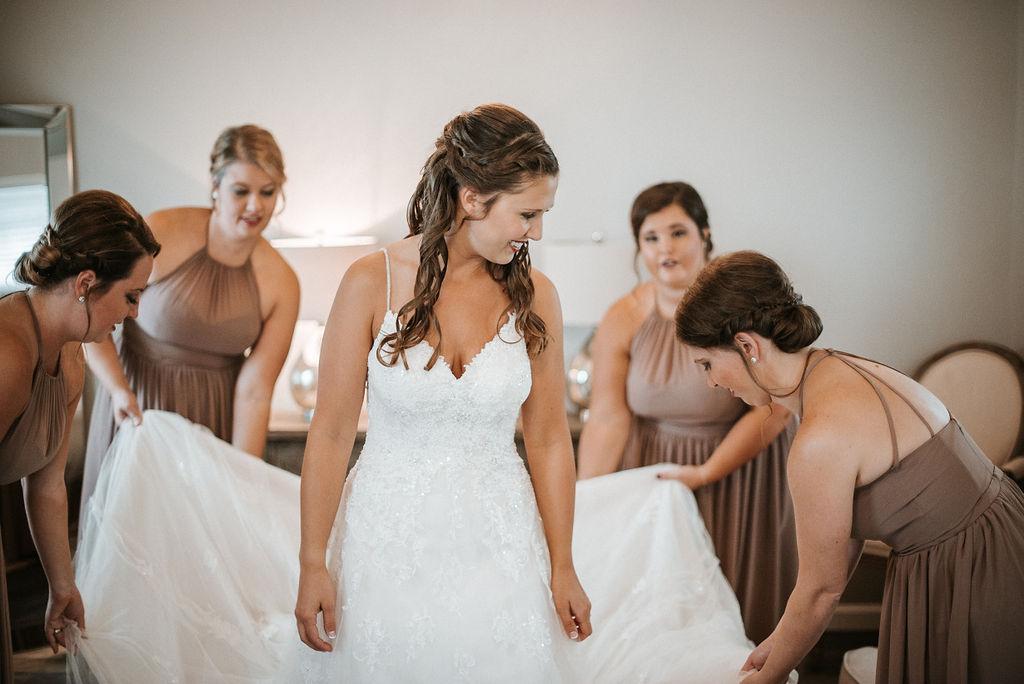 bridesmaids helping bride into wedding dress at 48 Fields Farm