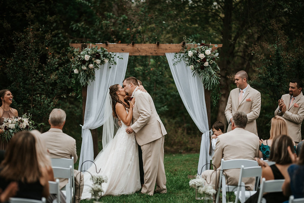 bride and groom kissing at the alter at 48 Fields Farm