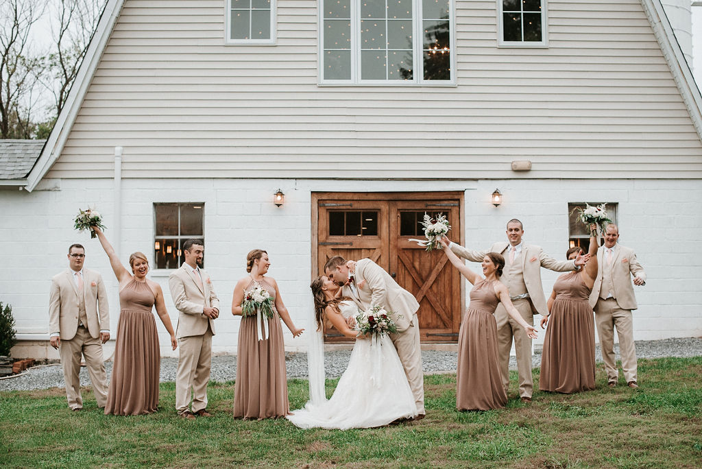 wedding party cheering as bride and groom kiss at 48 Fields Farm