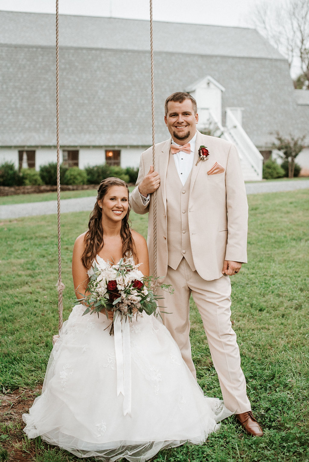 bride and groom smiling on a swing at 48 Fields Farm