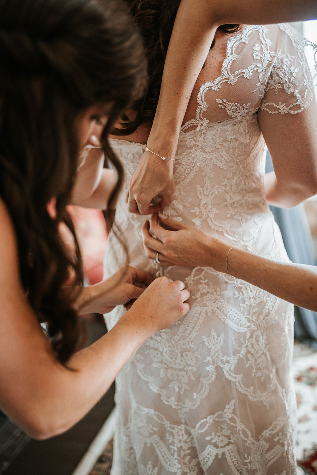 bridesmaids helping bride get in to wedding dress at Khimaira Farm