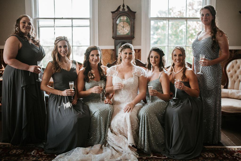 Bride and bridesmaids smiling and drinking champagne at Khimaira Farm