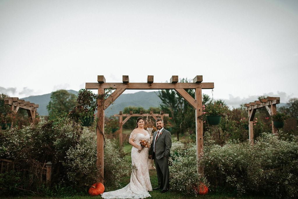 bride and groom posing at the gardens at Khimaira Farm