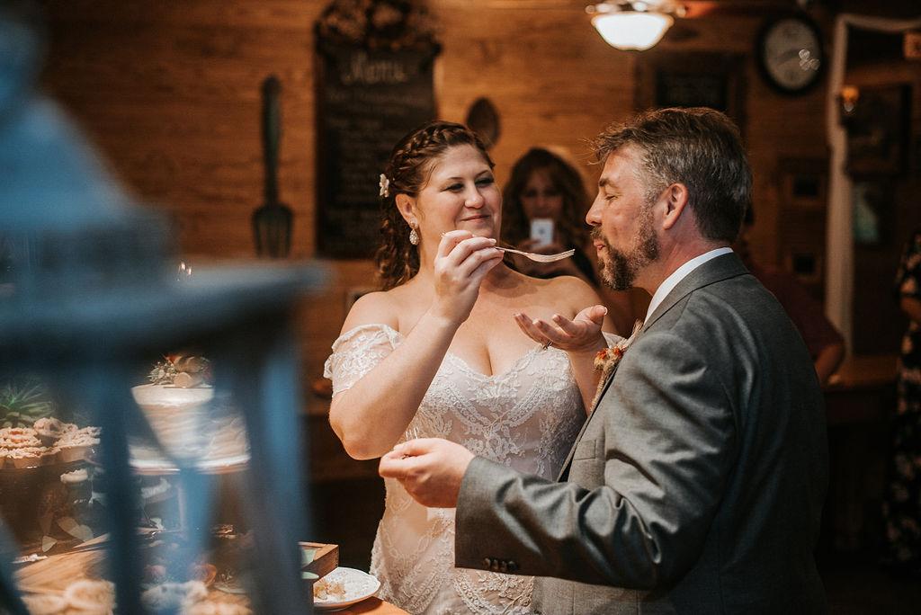 bride and groom eating wedding cake at Khimaira Farm