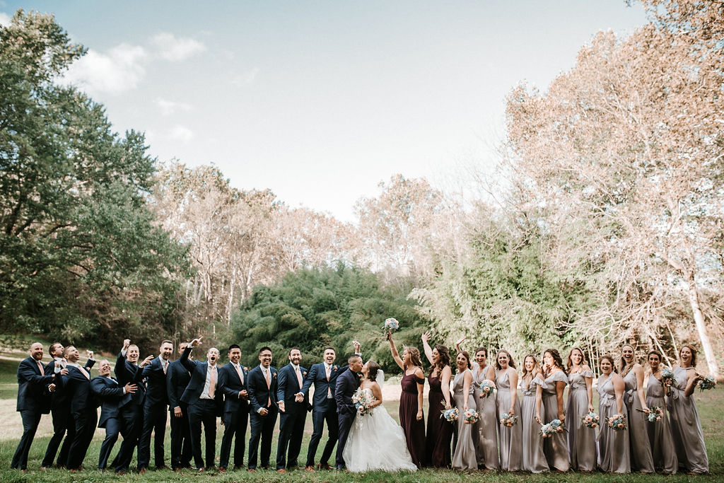 wedding party cheering as bride and groom kiss at kimble farm