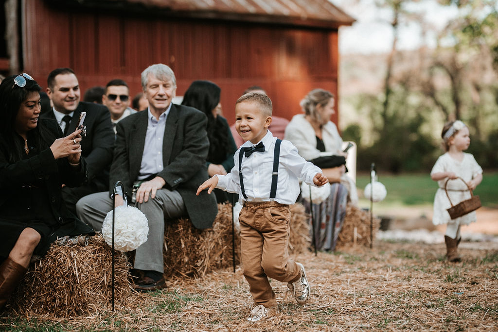 ring bearer and flower girl walking up the aisle at kimble farm