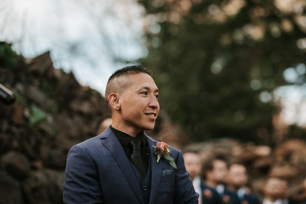 groom looking at bride as she walks up the aisle at kimble farm