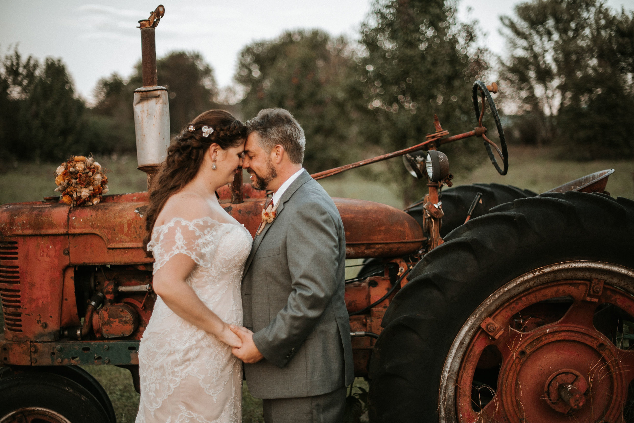 bride and groom holding hands in front of tractor at Khimaira Farm