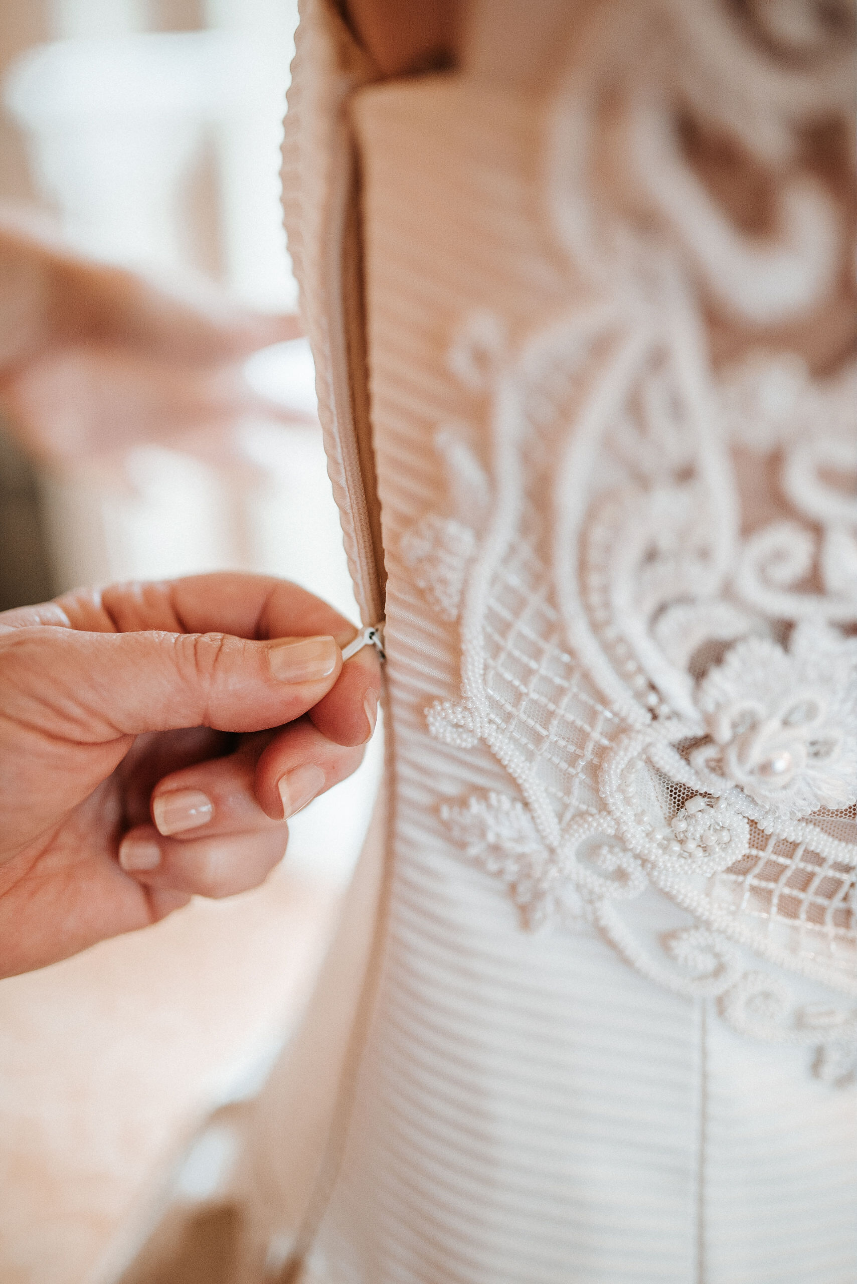 Bride getting zipped up in wedding dress at St. Mark Orthodox Church