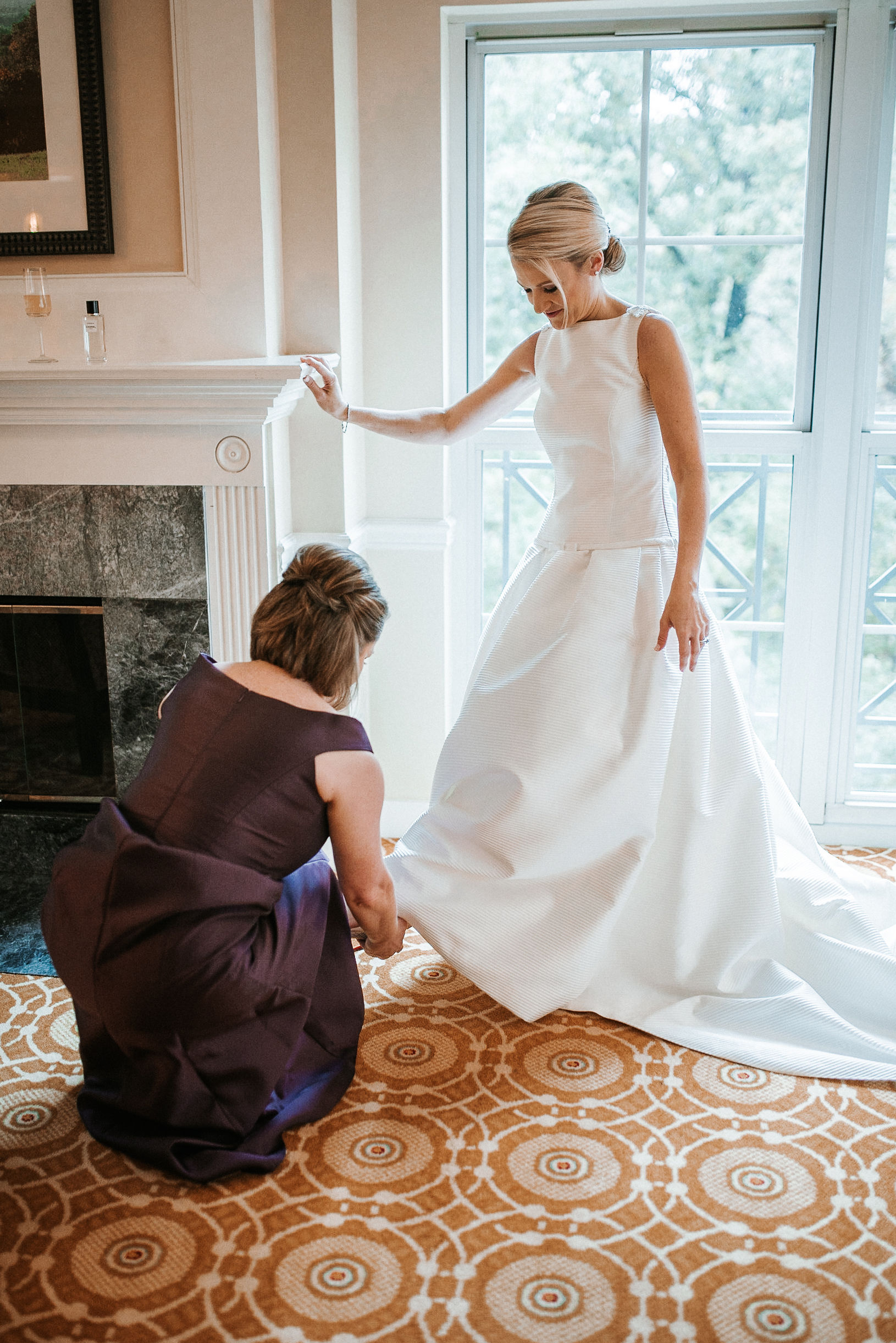 bridesmaid helping bride put on shoe at St. Mark Orthodox Church