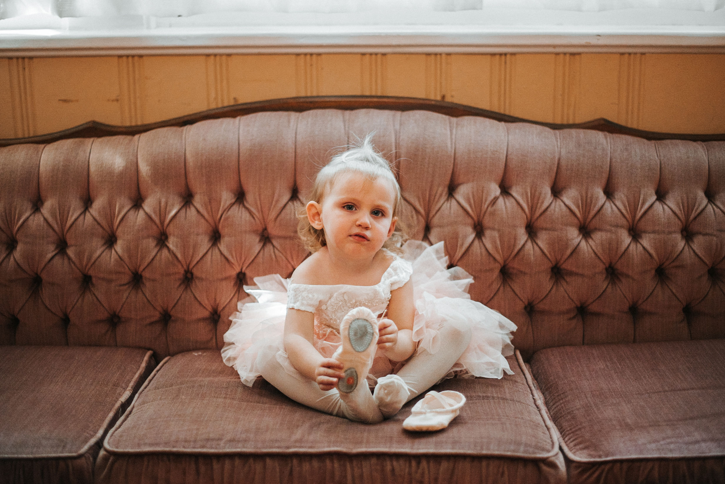 flower girl sitting on the couch at the inn at the silk mill