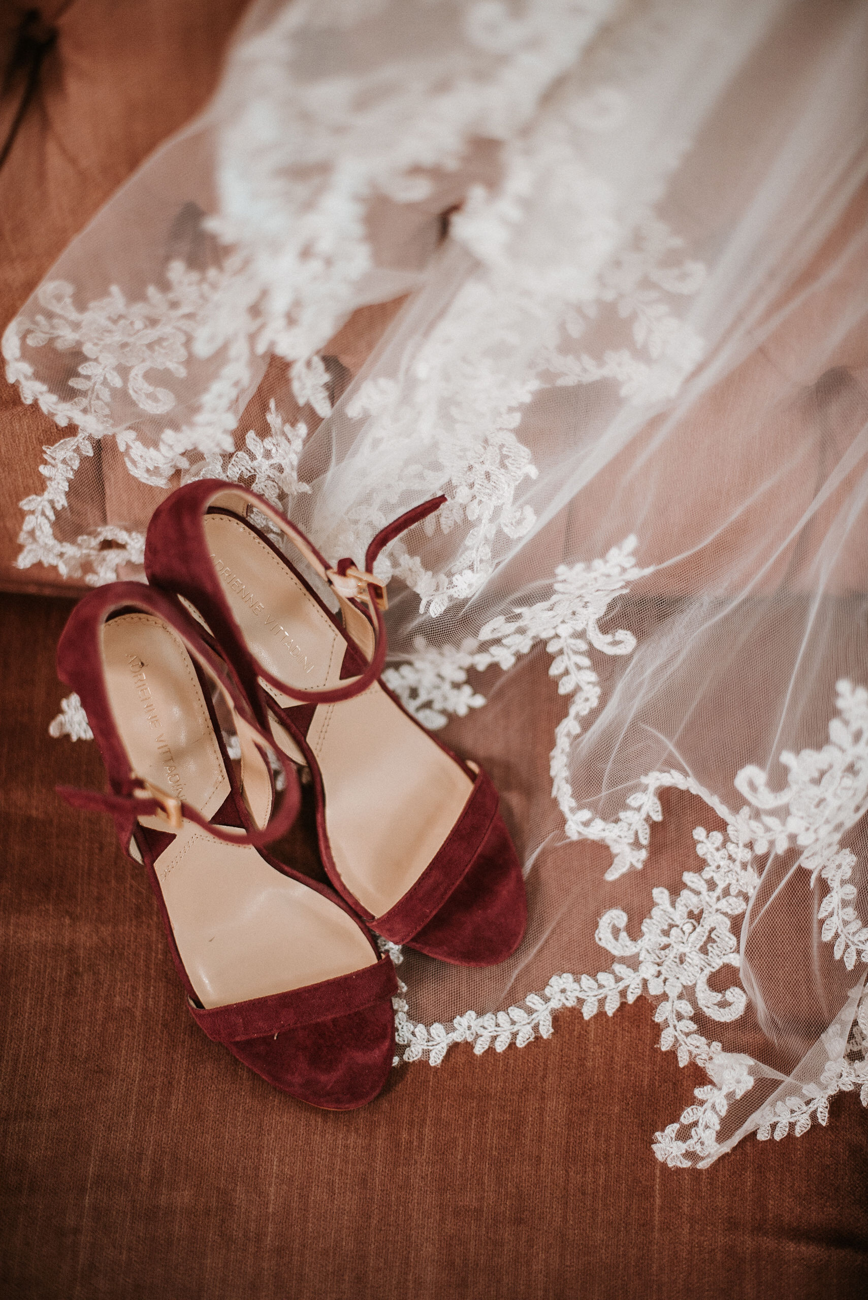 detail shot of bride's wedding shoes and veil at the inn at the silk mill