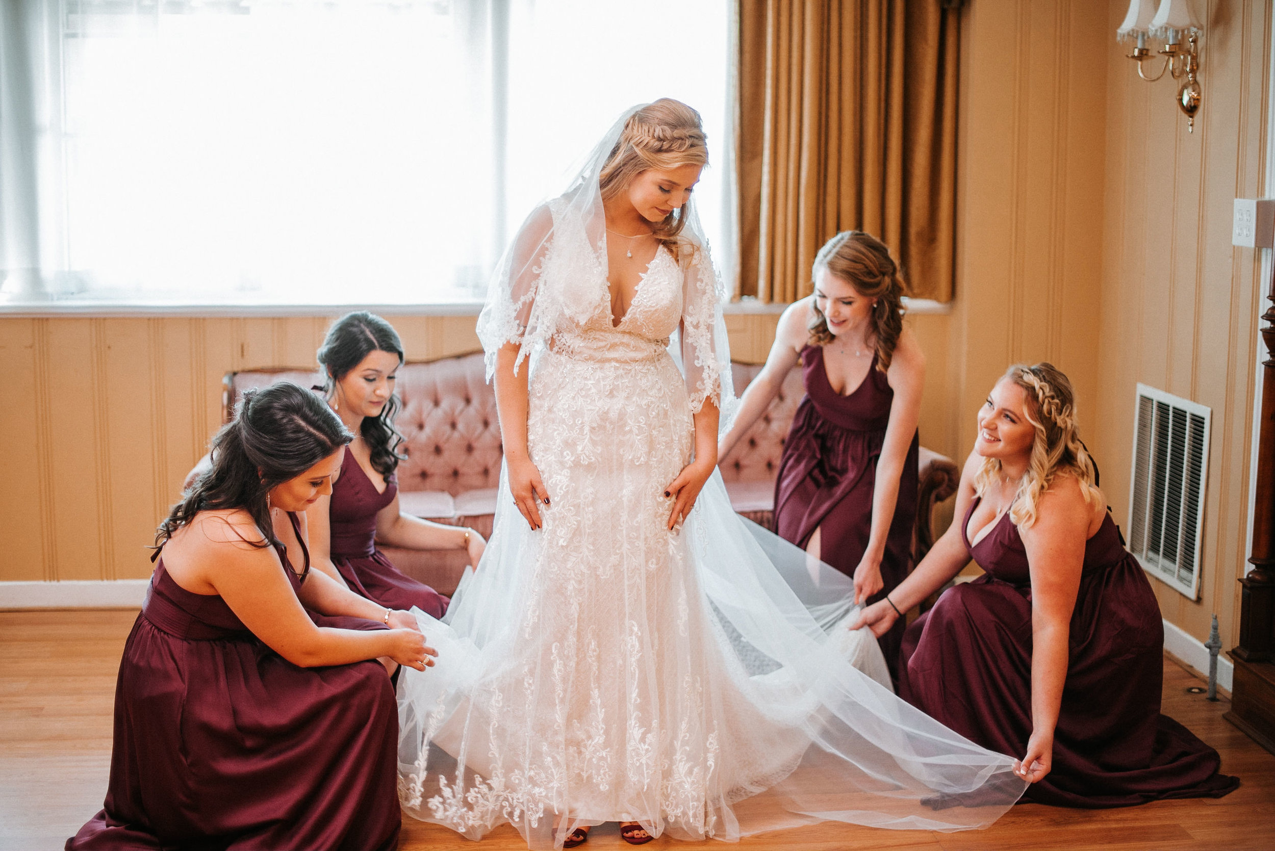 bridesmaids helping bride get ready at the inn at the silk mill