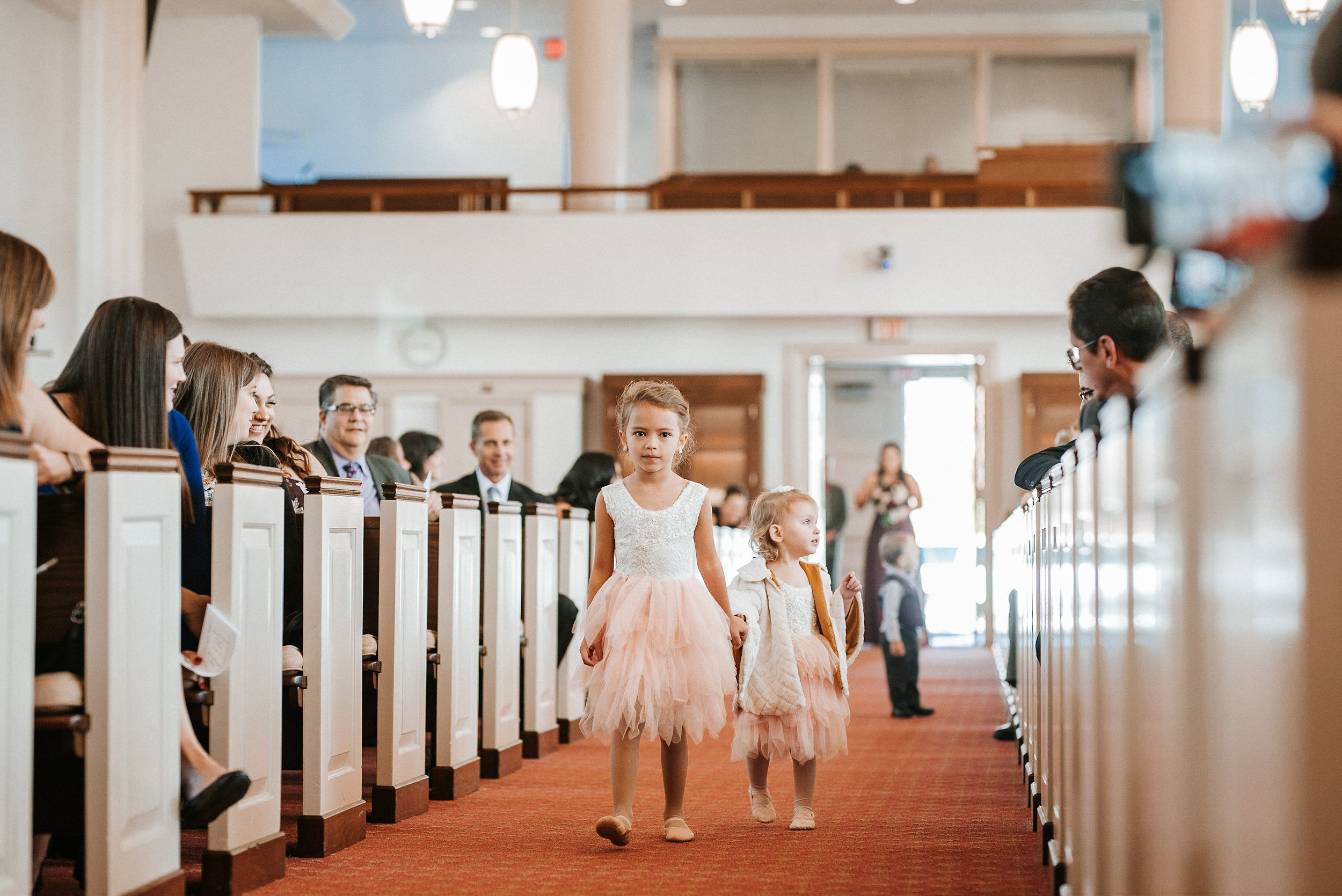 flower girls walking down the aisle at the united states marine corps memorial chapel