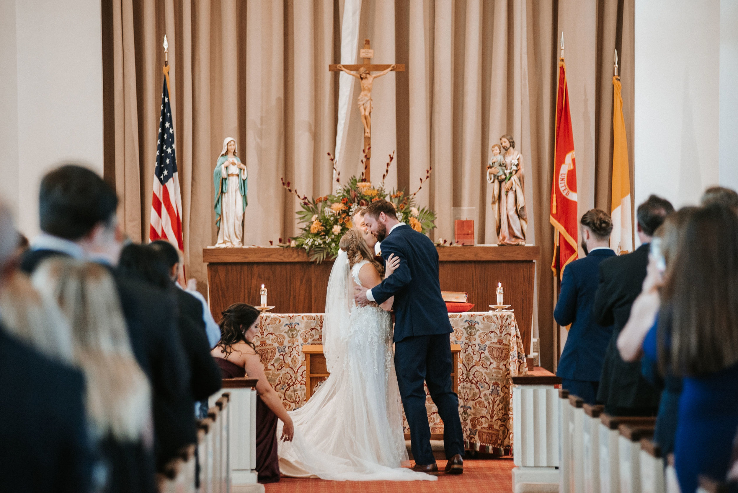 bride and groom kissing at the alter at the united states marine corps memorial chapel