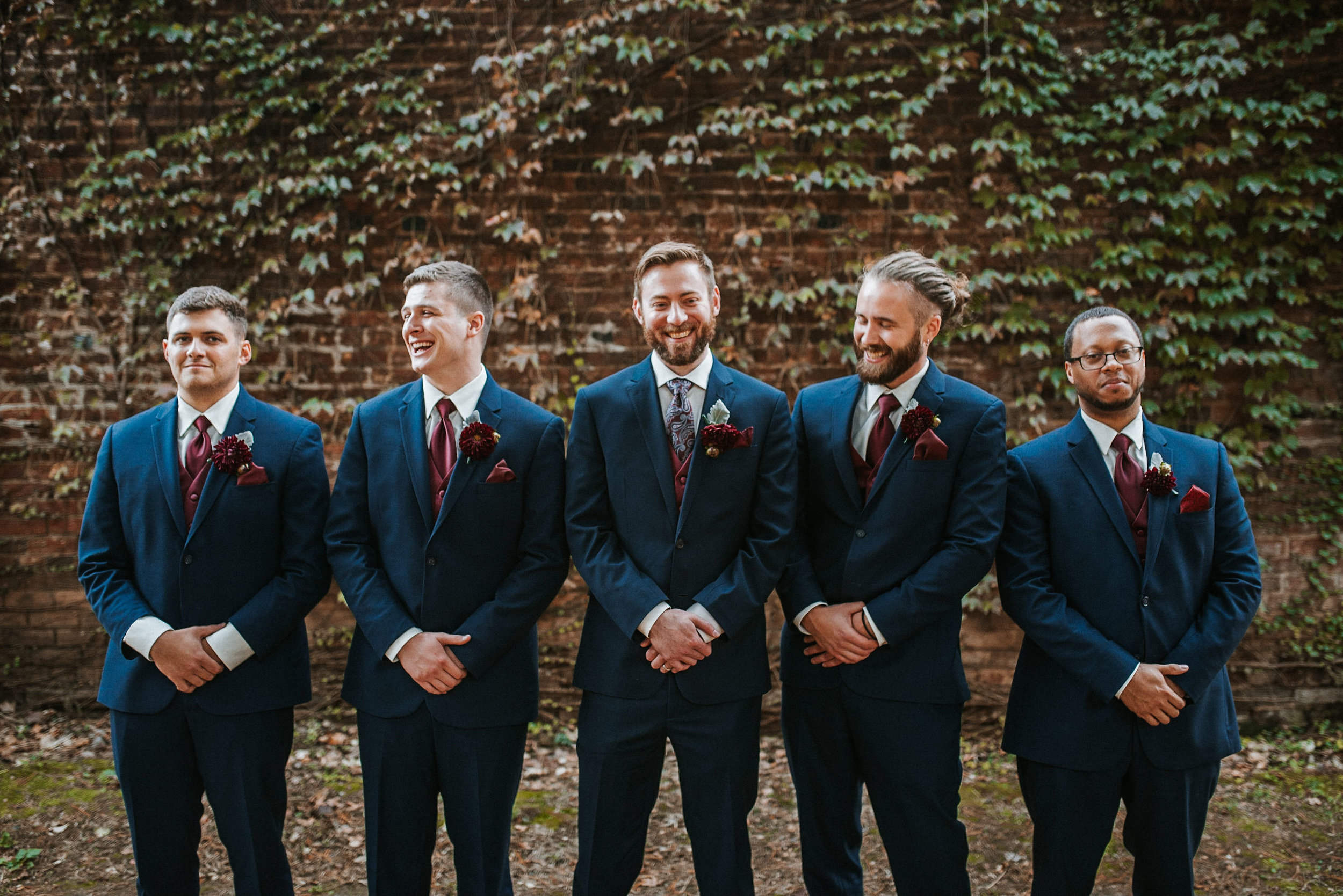groomsmen and groom laughing at the inn at the silk mill