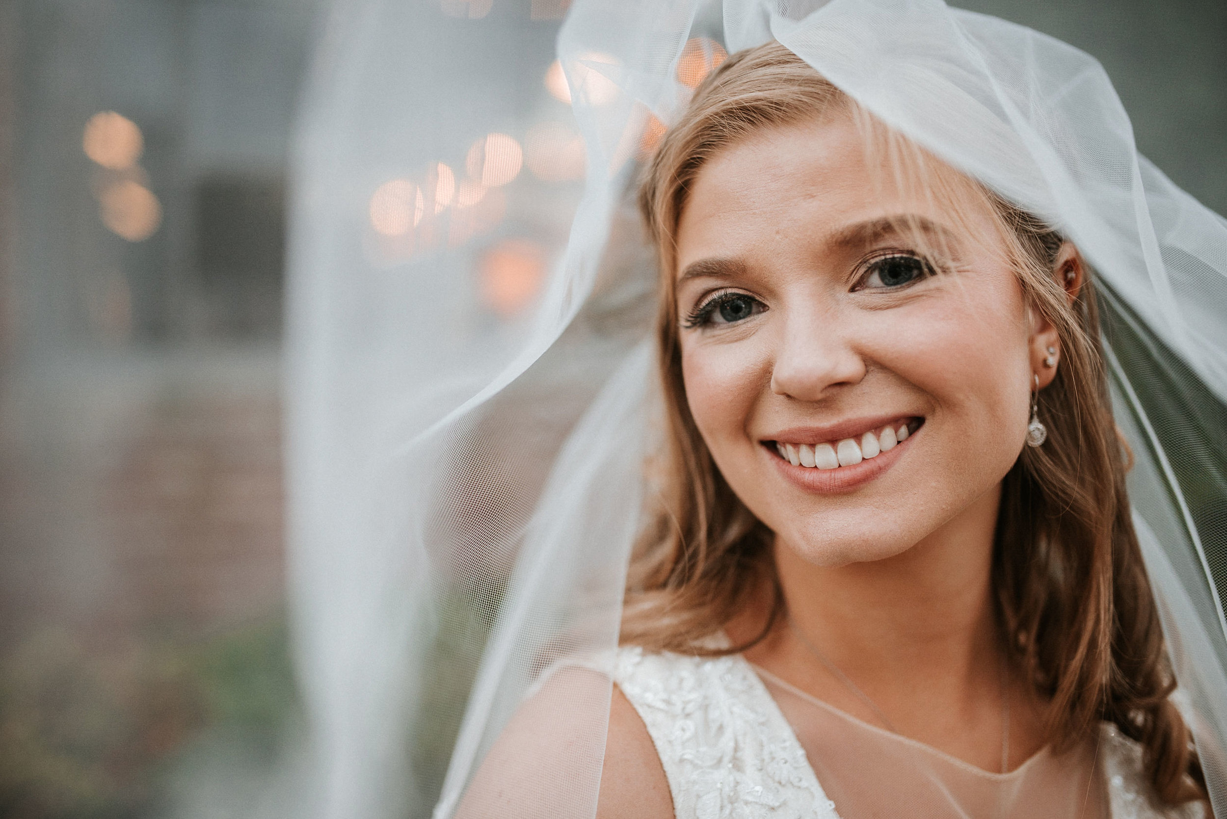 bride smiling under veil at the inn at the silk mill