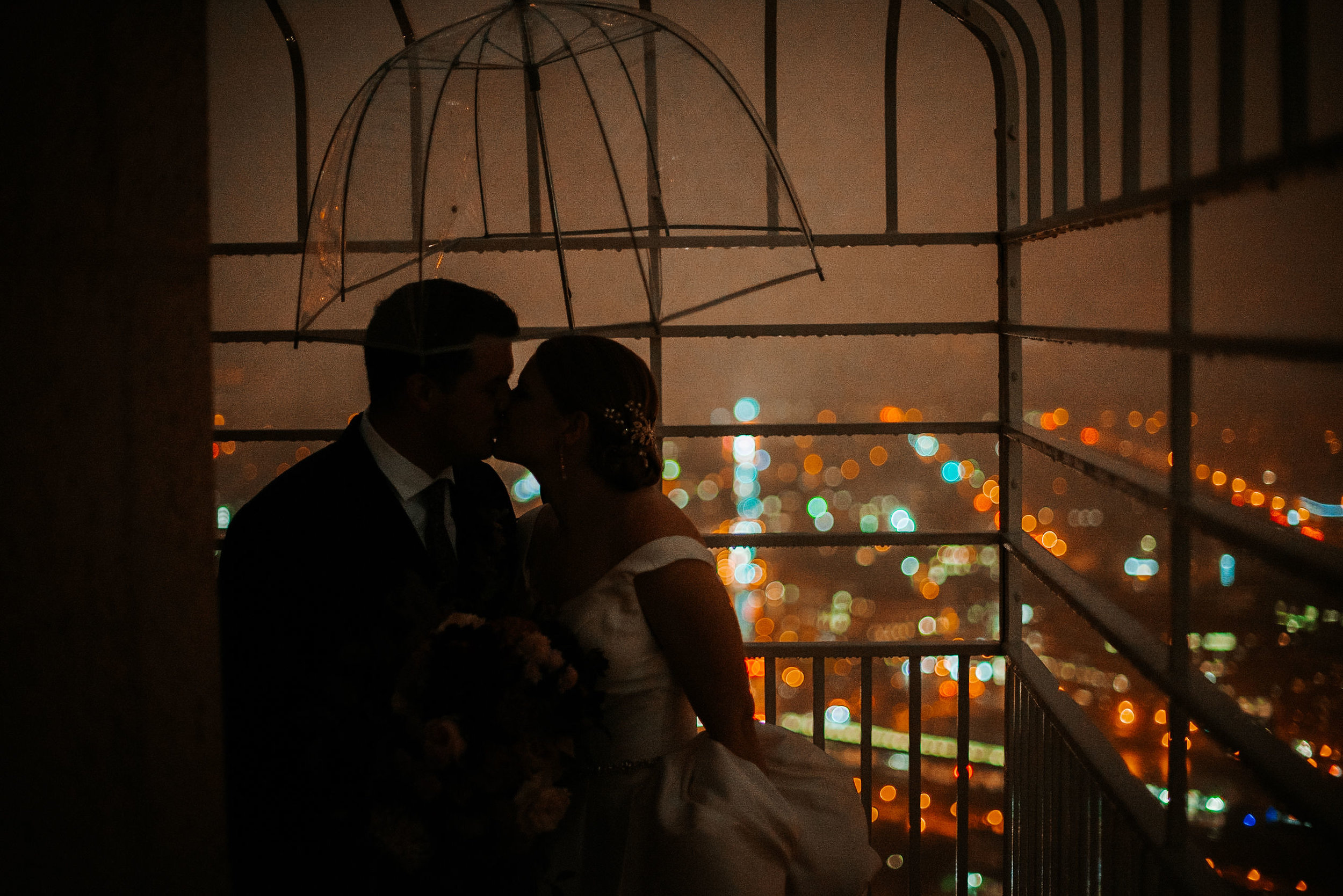 bride and groom kissing in the rain at The George Washington Masonic National Memorial