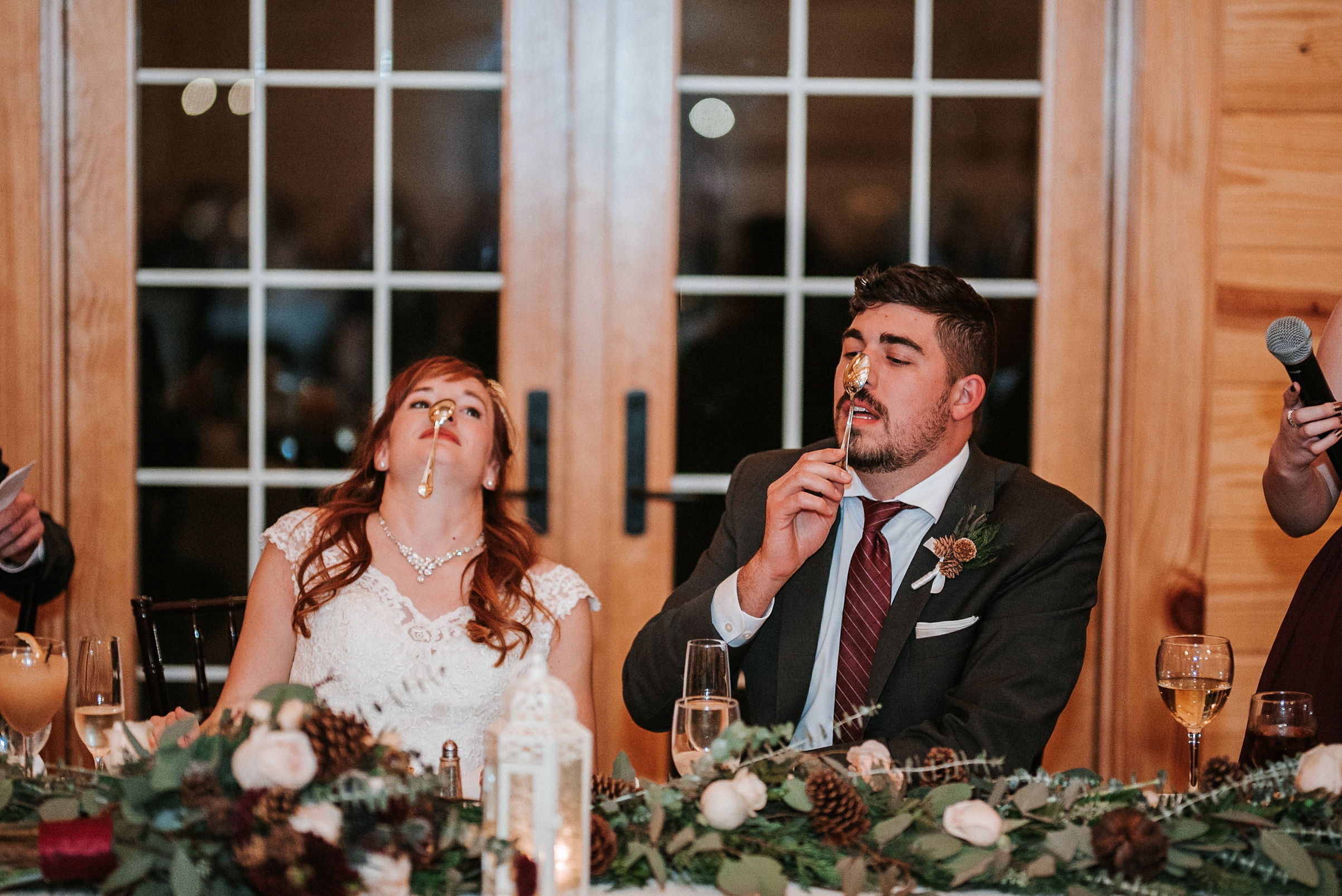 bride and groom hanging spoons on nose at The Middleburg Barn at Fox Chase Farm