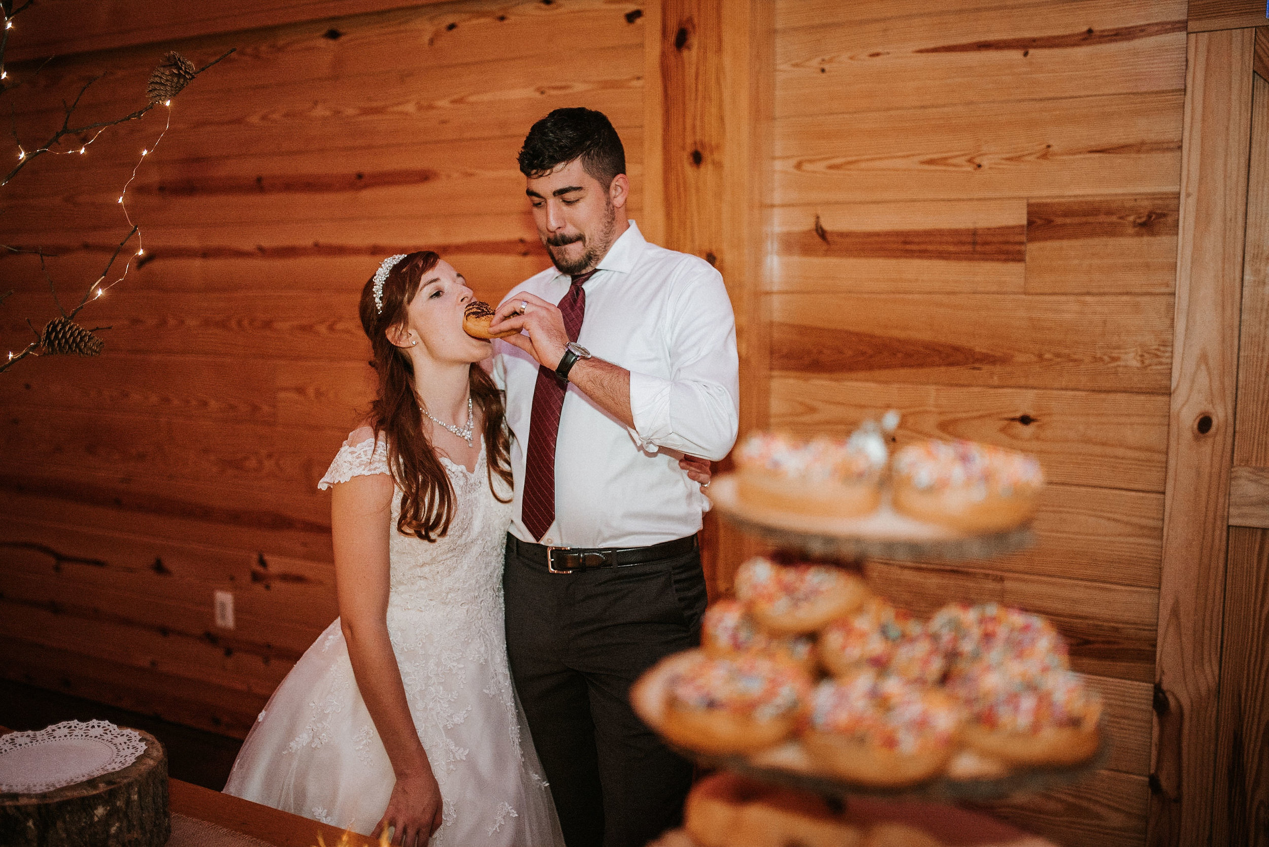 bride and groom eating donuts at The Middleburg Barn at Fox Chase Farm