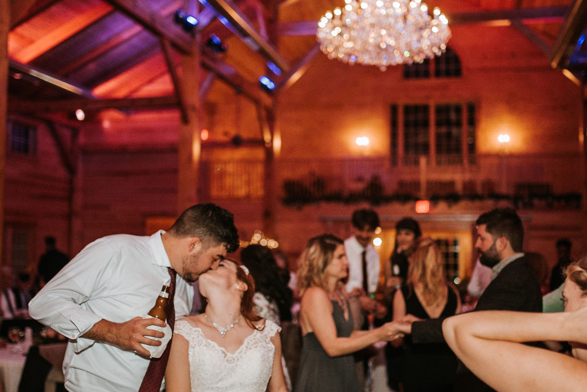 bride and groom kissing at reception at The Middleburg Barn at Fox Chase Farm