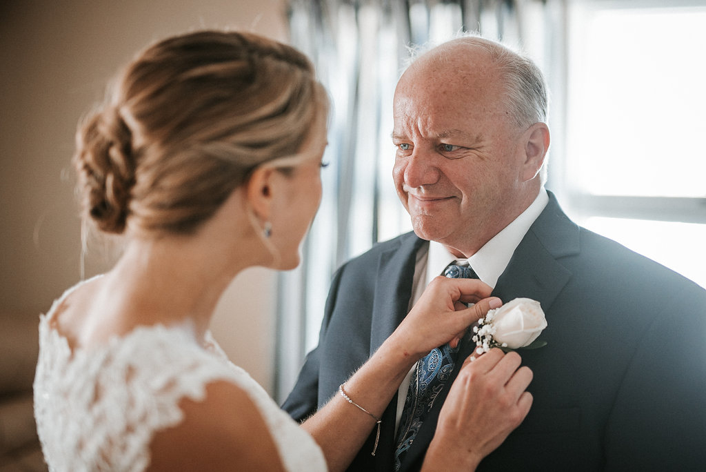 bride pinning boutonniere on father