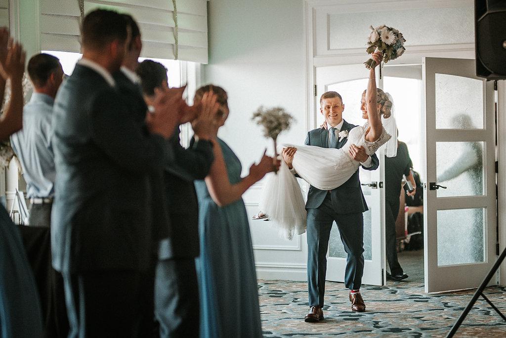 groom carrying bride in to reception