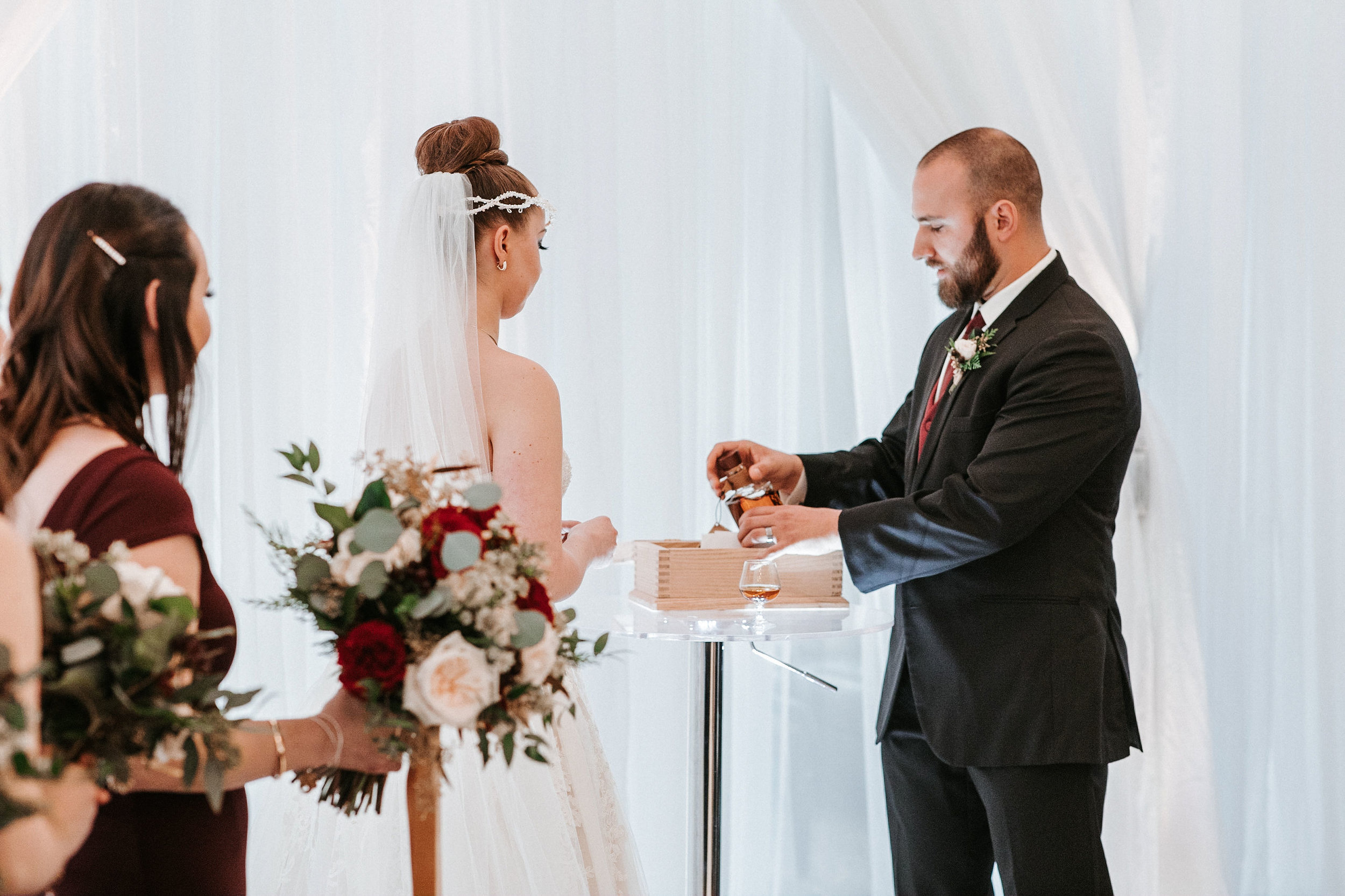 groom pouring a drink at ceremony at Whitehall Estate