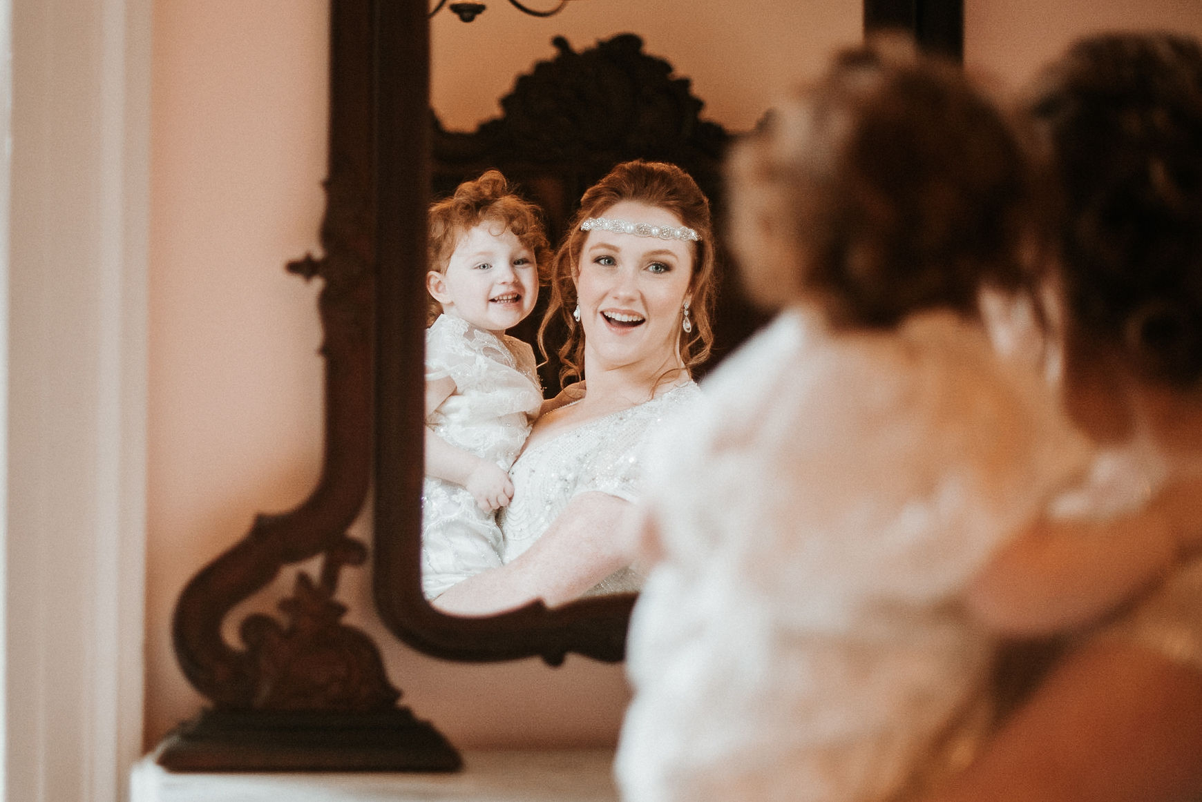 Bride and her daughter looking in a mirror.