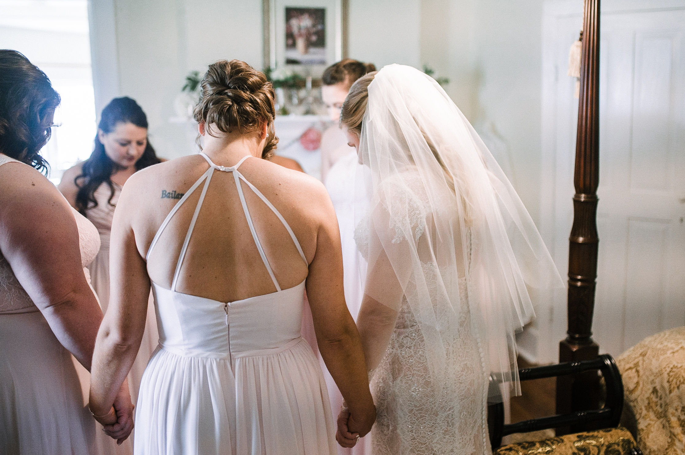 bride and bridesmaids praying before wedding at Rixey Manor