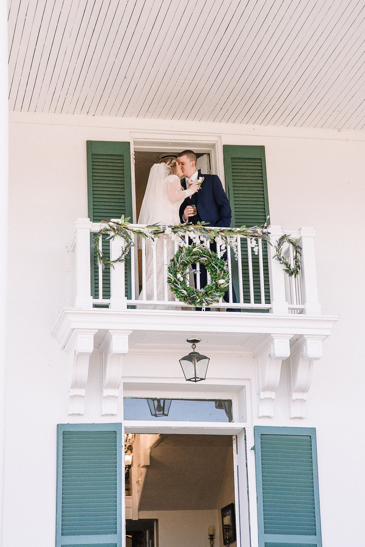 bride and groom kissing on balcony at Rixey Manor