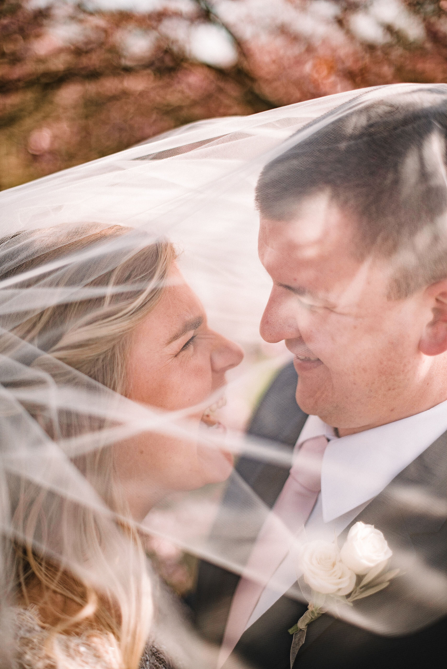 bride and groom smiling under veil at Rixey Manor