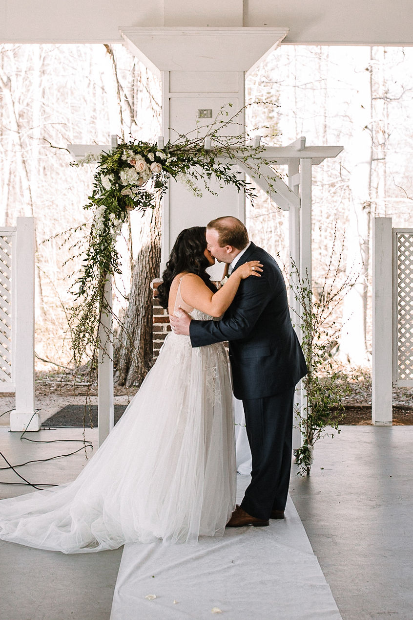 bride and groom kiss at the altar at Westfields Golf Club