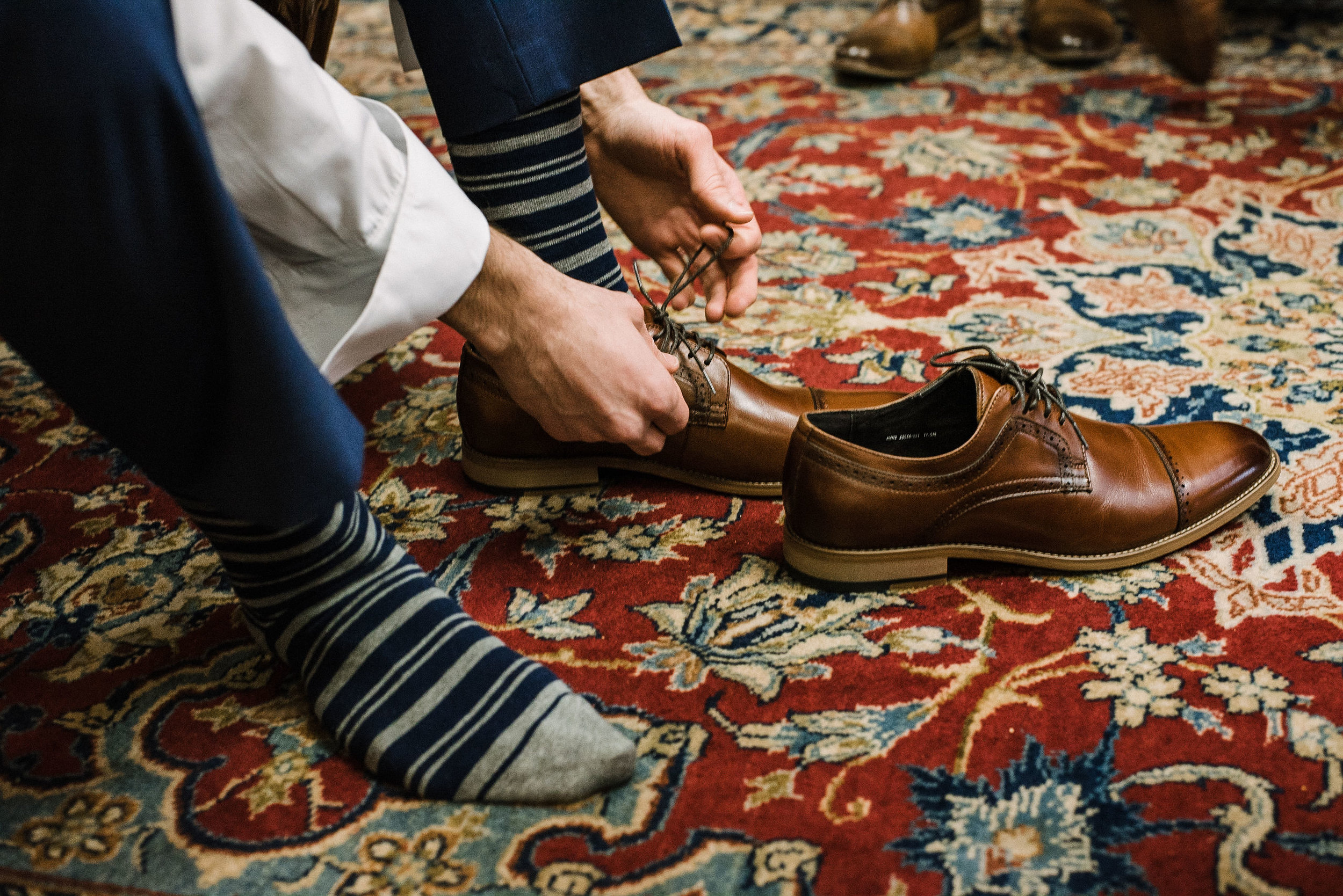 Groom putting on shoes at the Inn at the Old Silk Mill