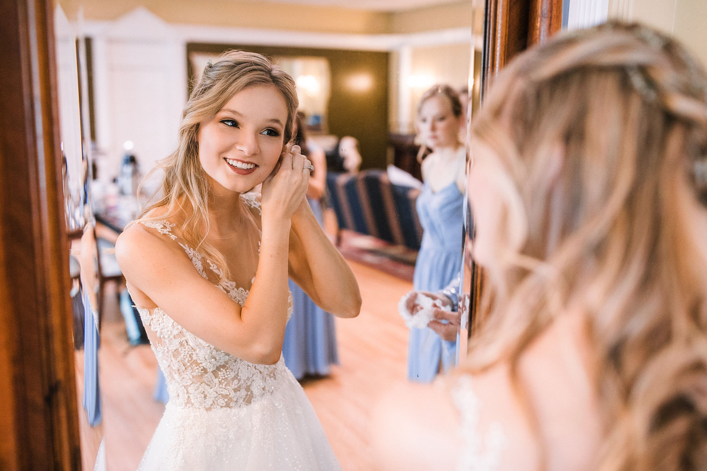 bride putting on earrings at the Inn at the Old Silk Mill