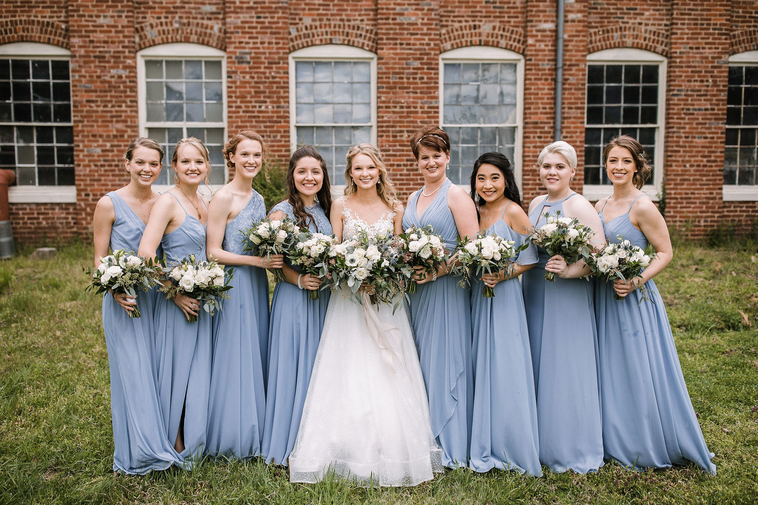 bride and bridesmaids posing at the Inn at the Old Silk Mill