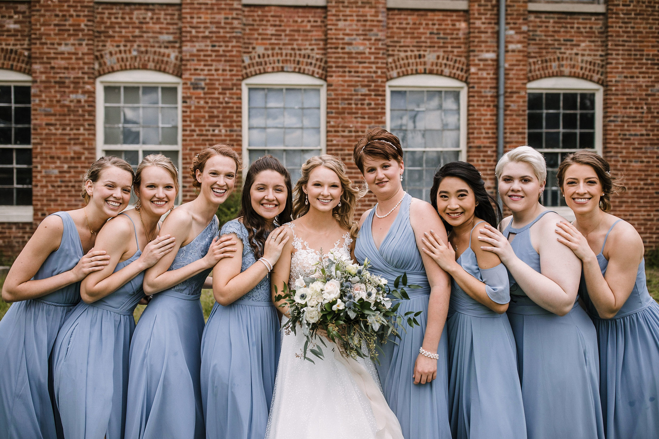 bride and bridesmaids smiling at the Inn at the Old Silk Mill