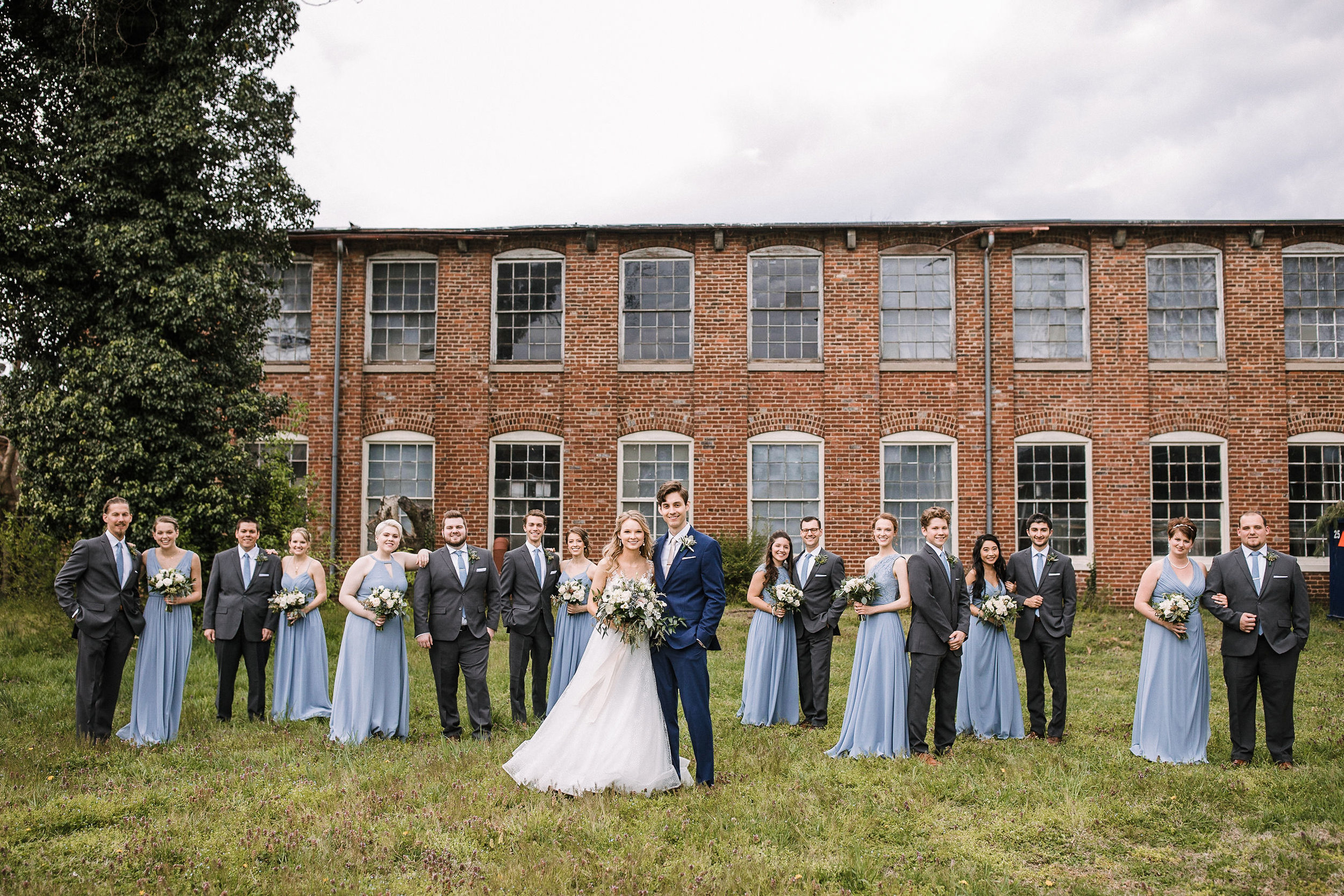wedding party posing with bride and groom at the Inn at the Old Silk Mill