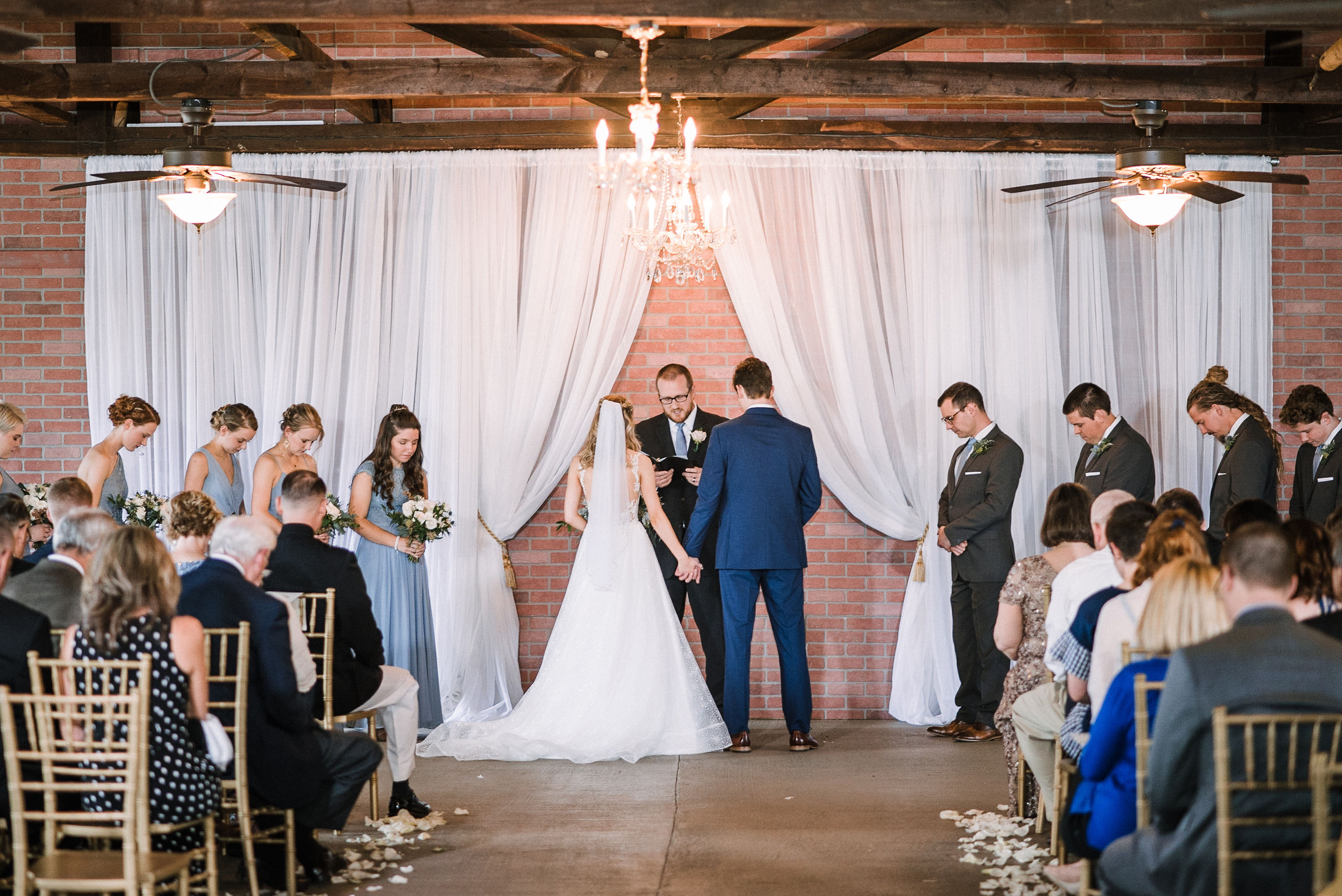 bride and groom holding hands at the altar at the Inn at the Old Silk Mill