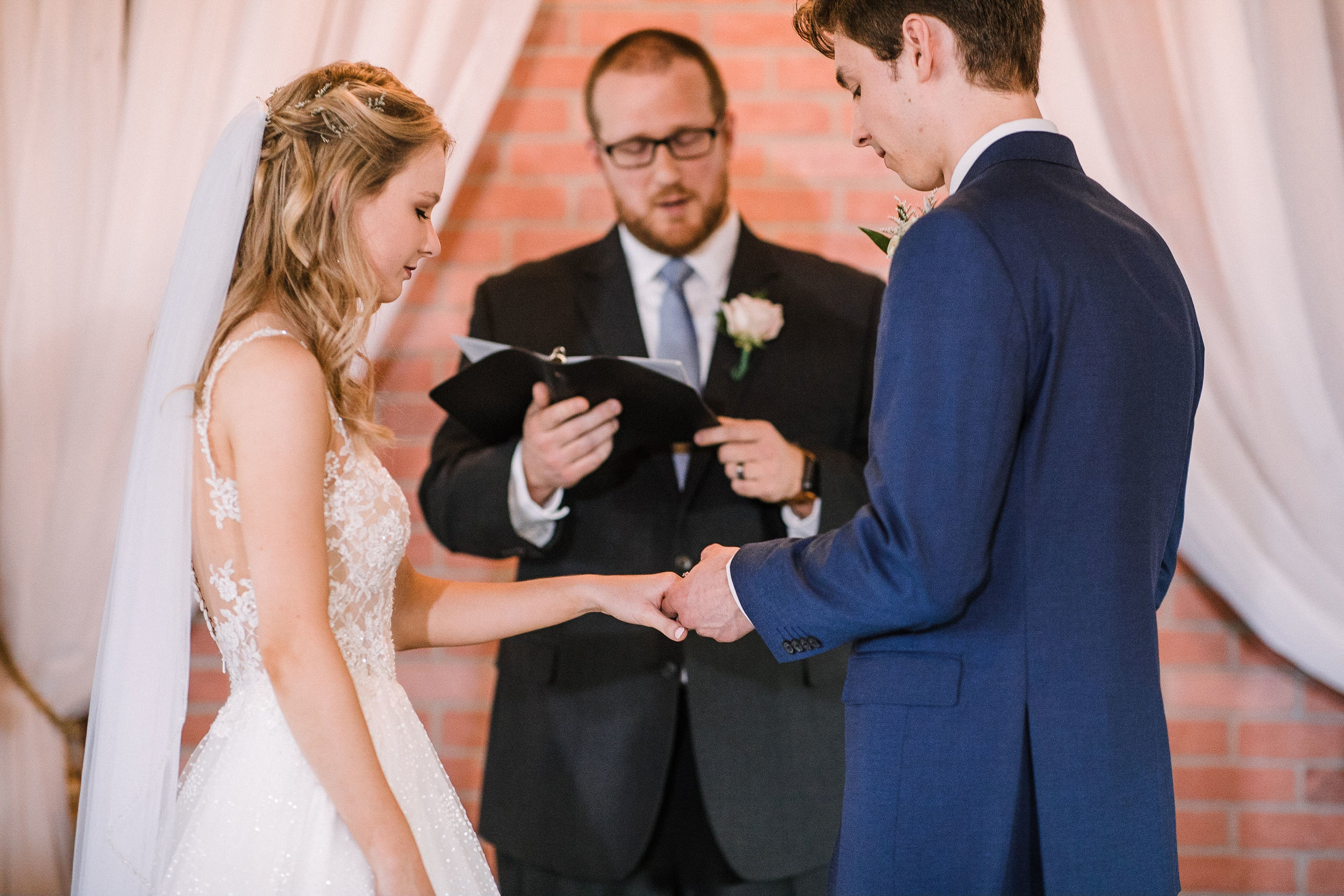 bride and groom exchanging rings at the Inn at the Old Silk Mill
