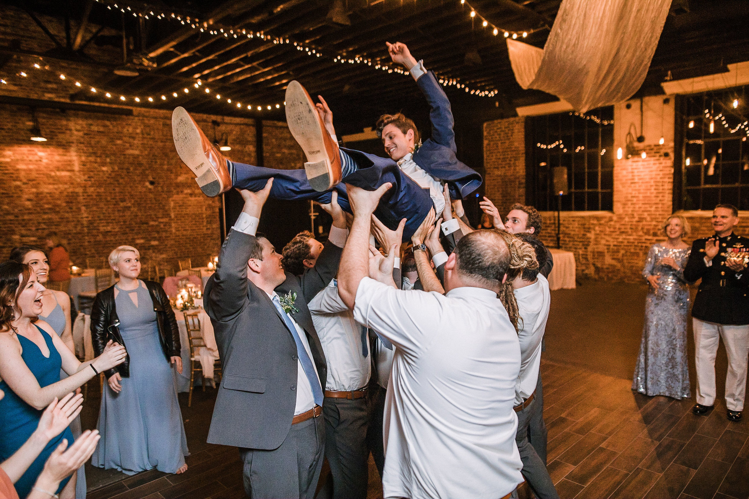 groom being carried by guests at the Inn at the Old Silk Mill