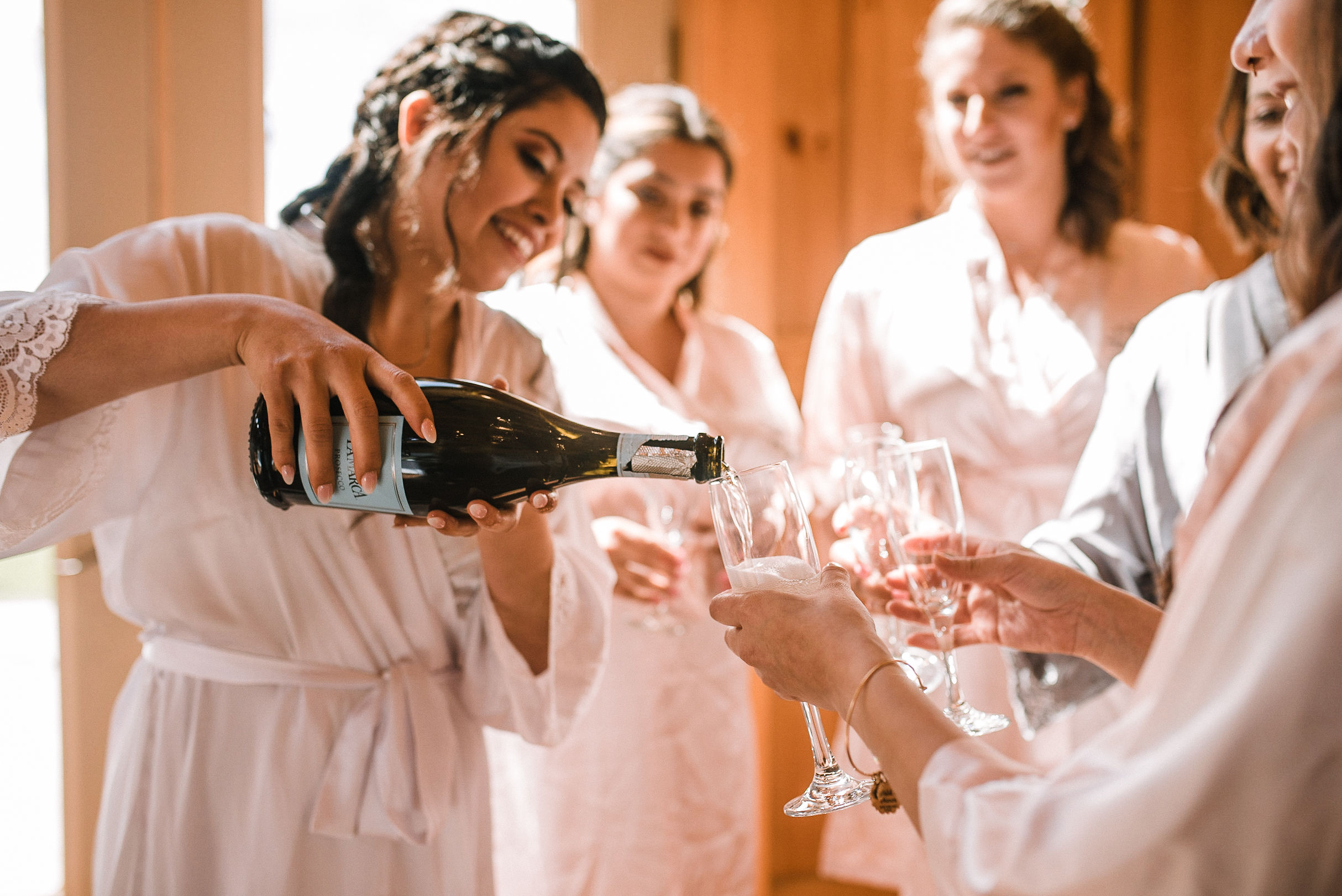 bride and bridesmaids drinking champagne at the Faithbrooke Barn & Vineyards