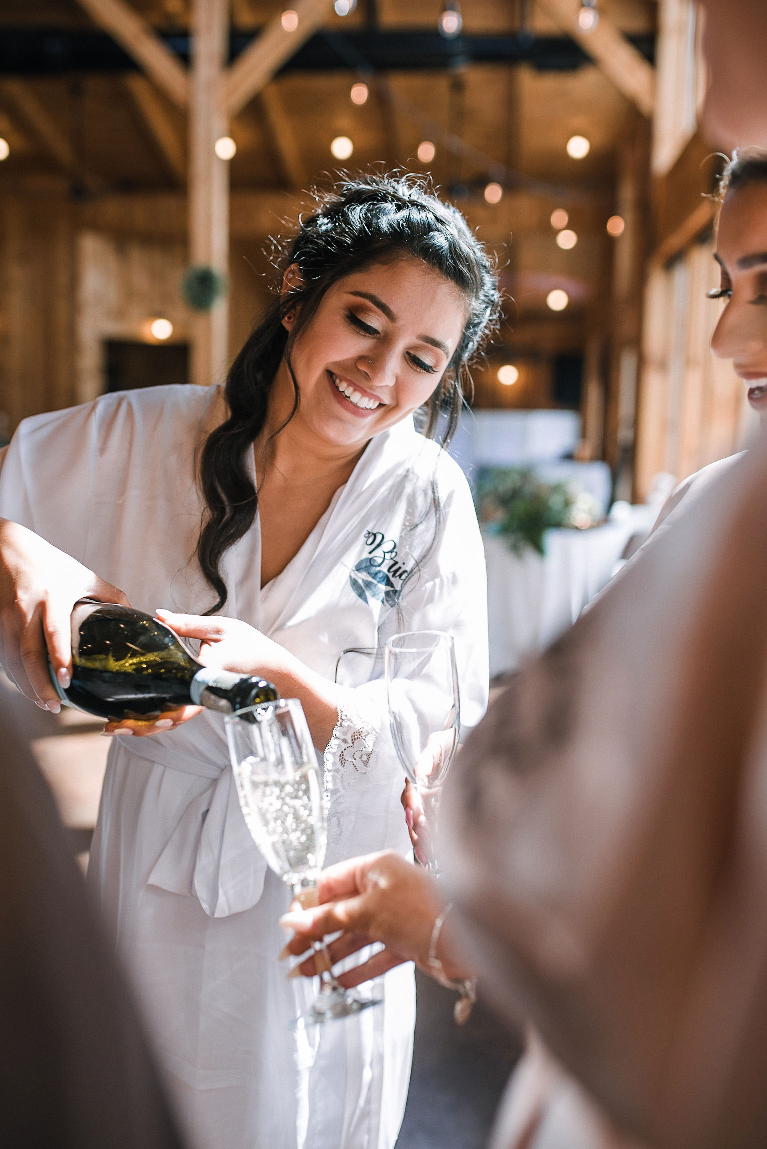 bride pouring champagne at the Faithbrooke Barn & Vineyards