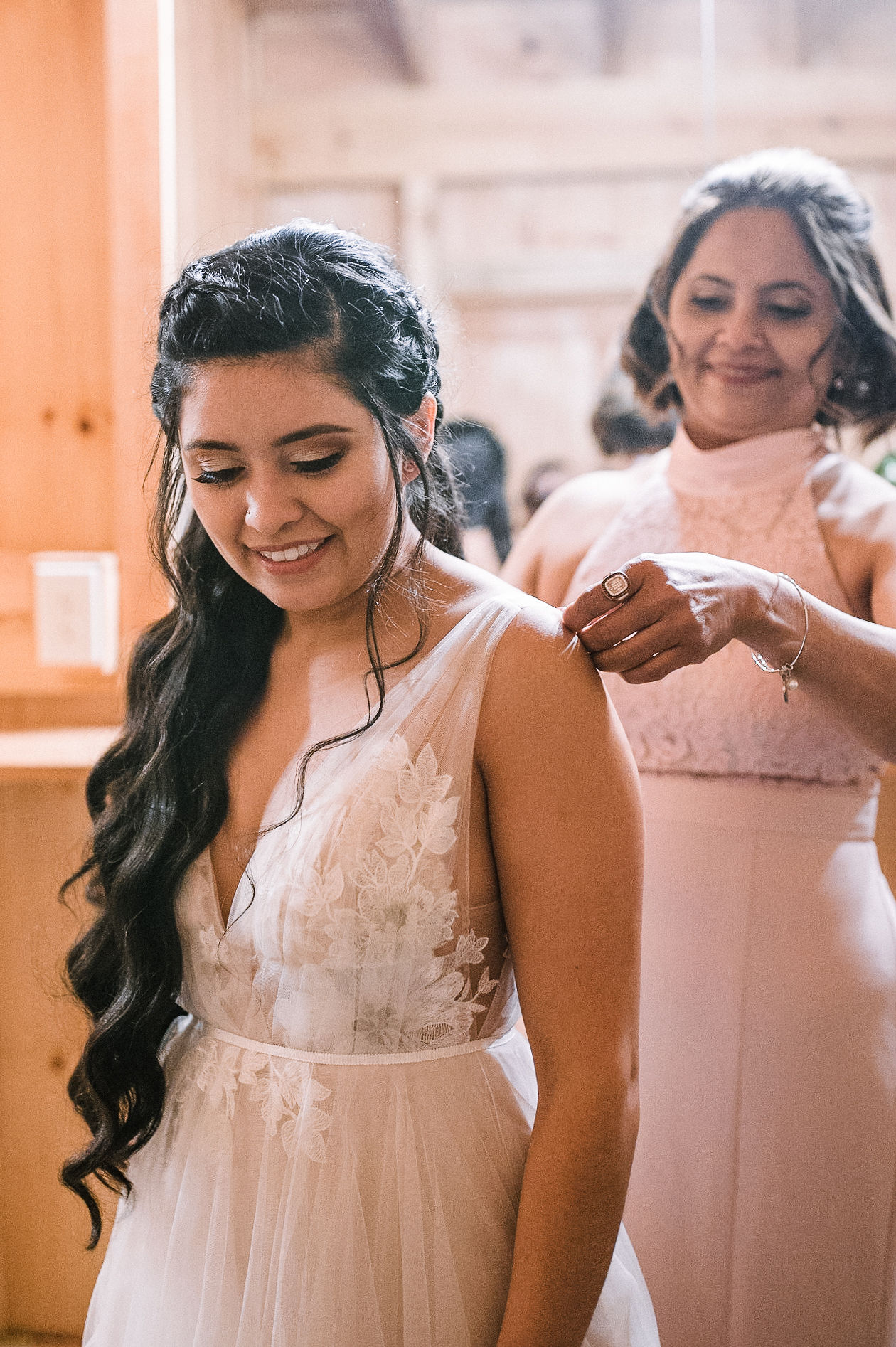 mother of the bride helping bride into wedding dress at the Faithbrooke Barn & Vineyards