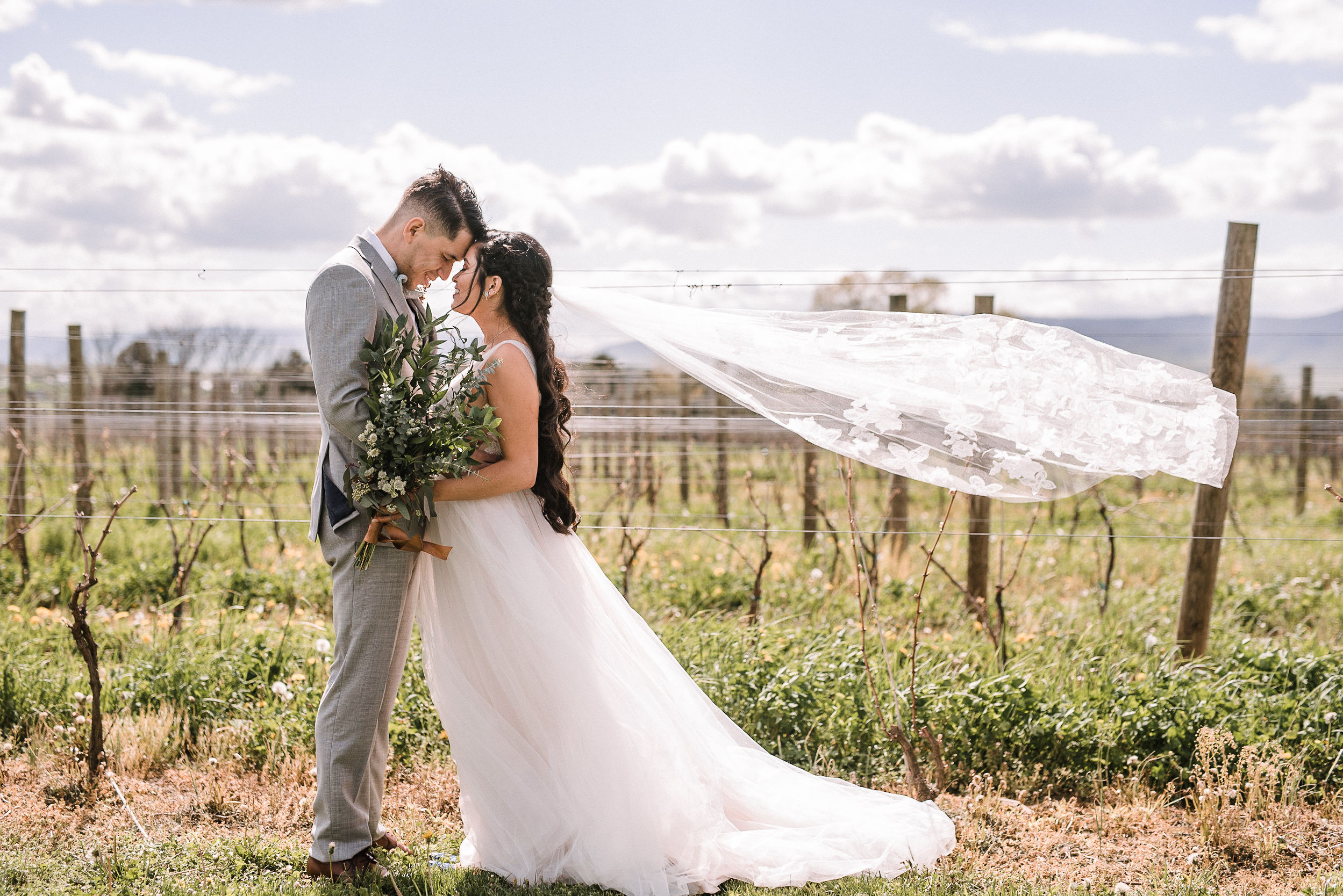 bride and groom embracing and veil is in the air at the Faithbrooke Barn & Vineyards