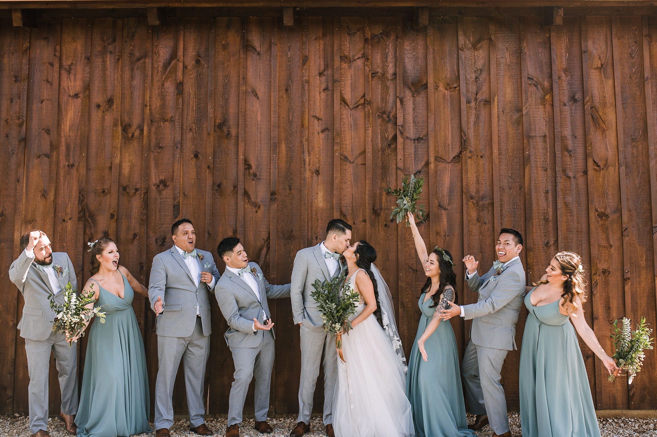 wedding party cheering as bride and groom kiss at the Faithbrooke Barn & Vineyards