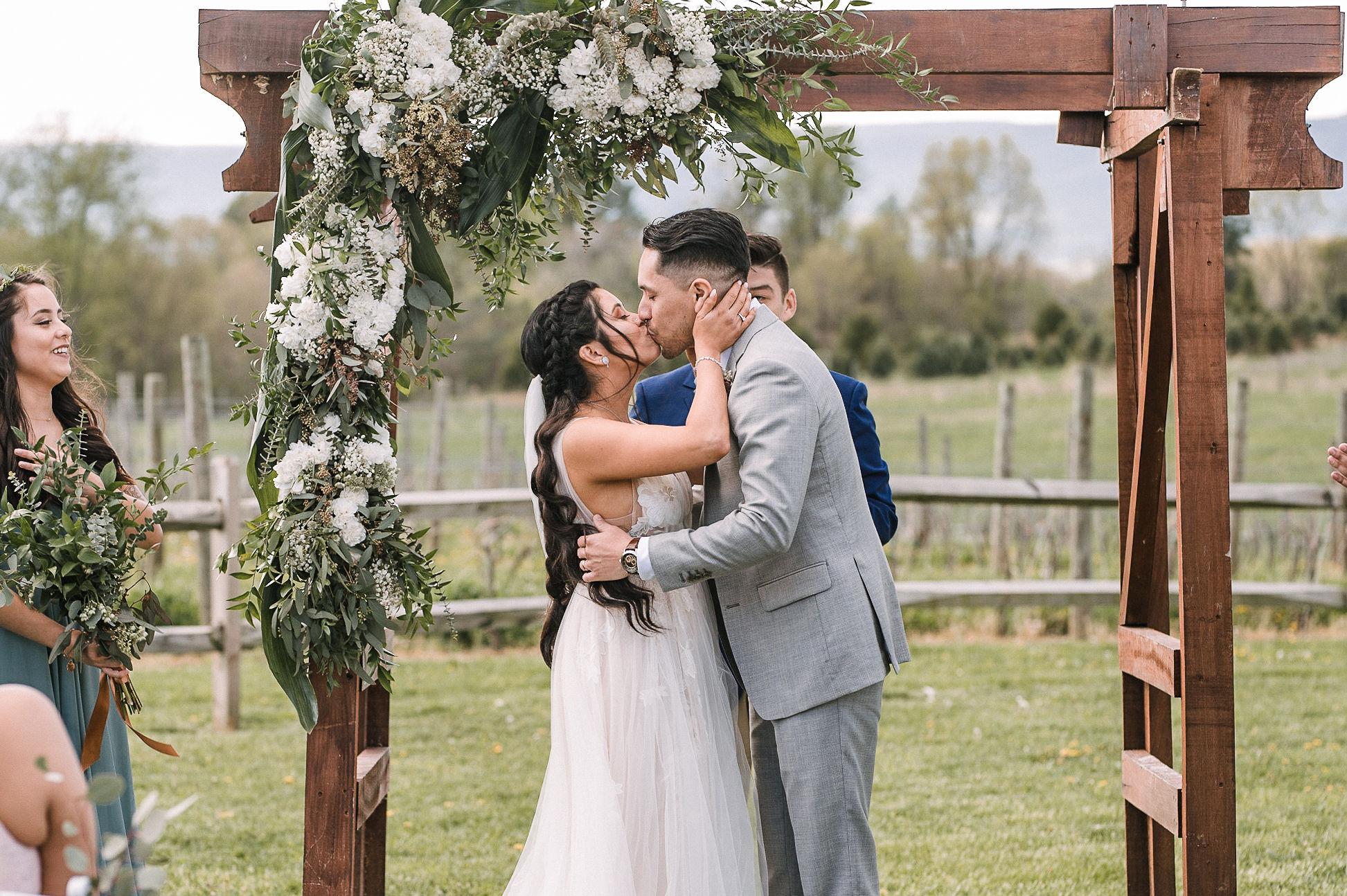 bride and groom kiss at altar at the Faithbrooke Barn & Vineyards