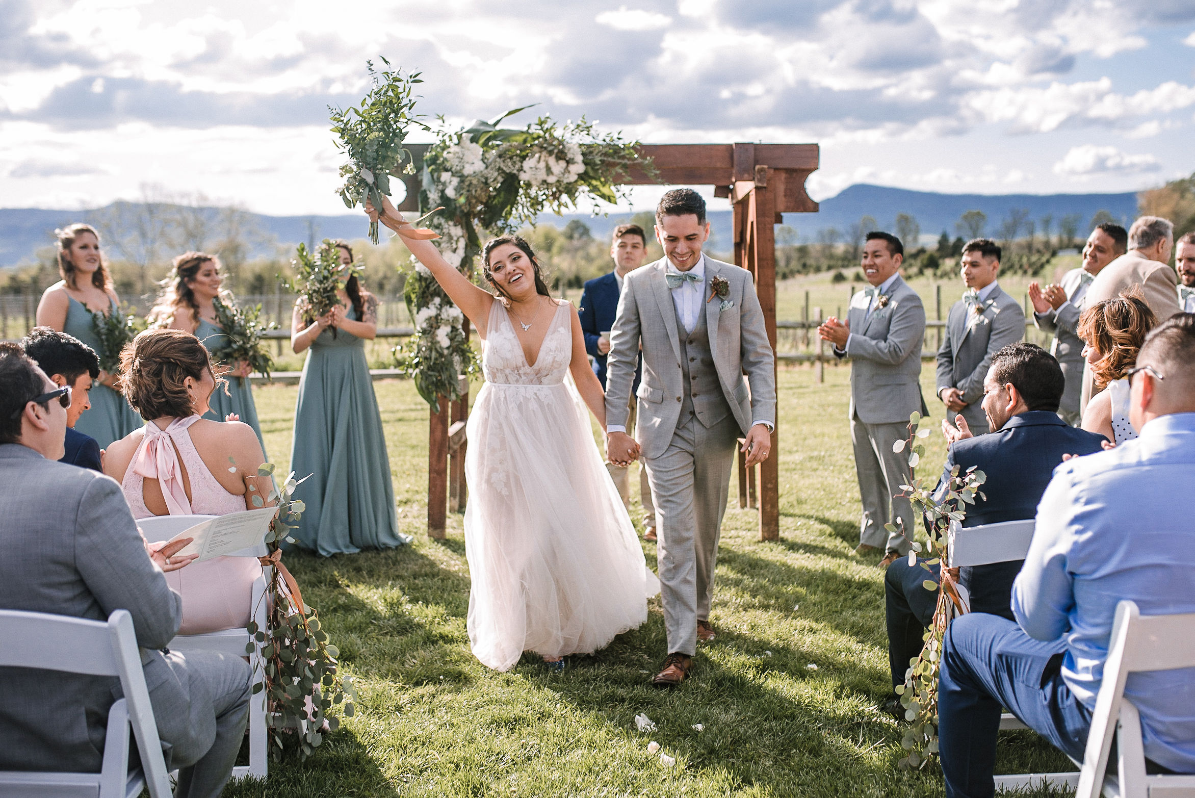 bride and groom smile and head up the aisle at the Faithbrooke Barn & Vineyards