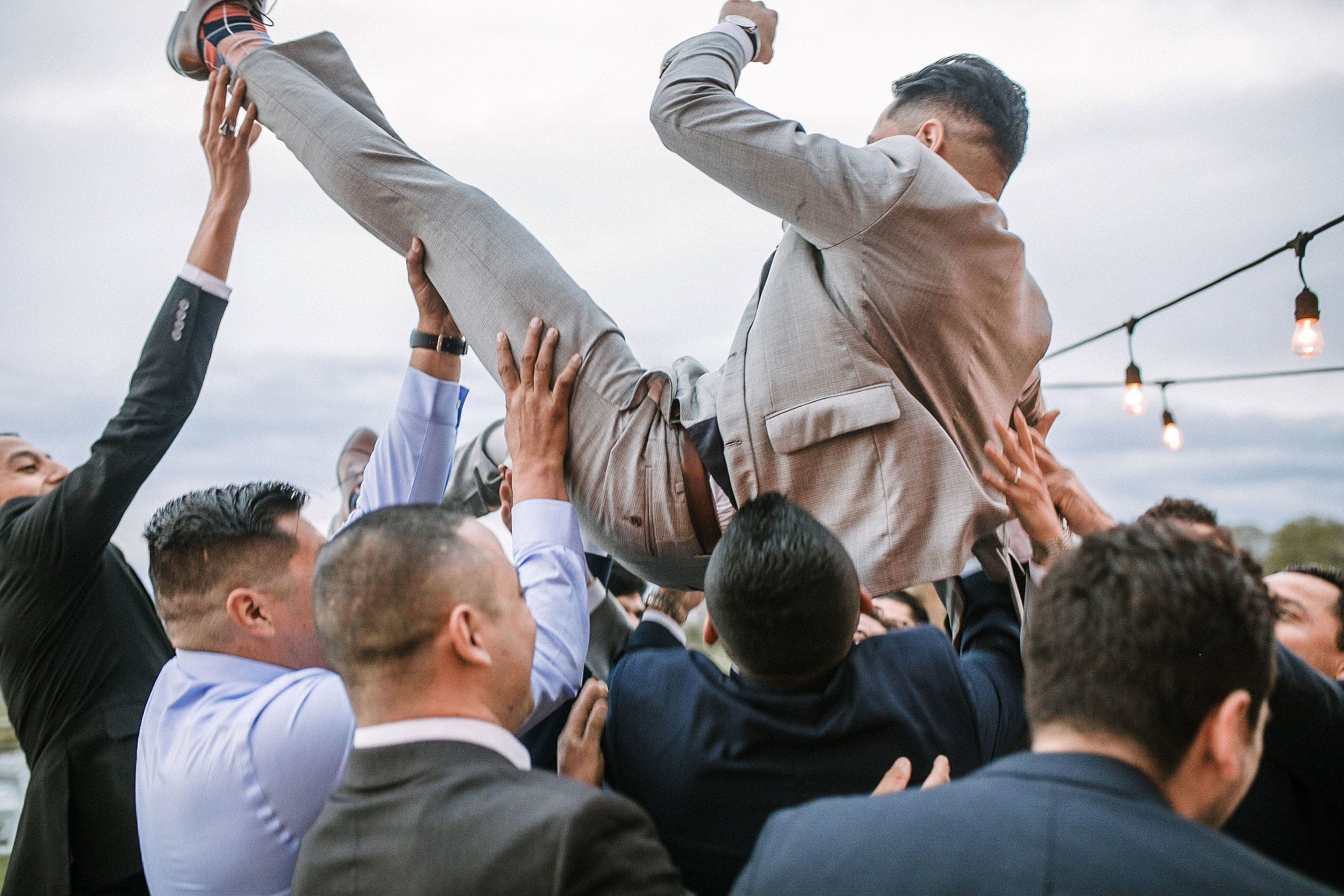 groom being carried by guests at the Faithbrooke Barn & Vineyards