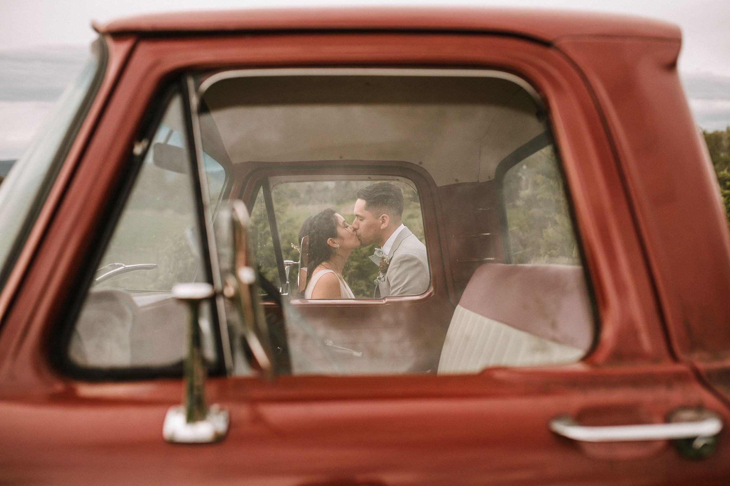 bride and groom kissing in window of truck at the Faithbrooke Barn & Vineyards